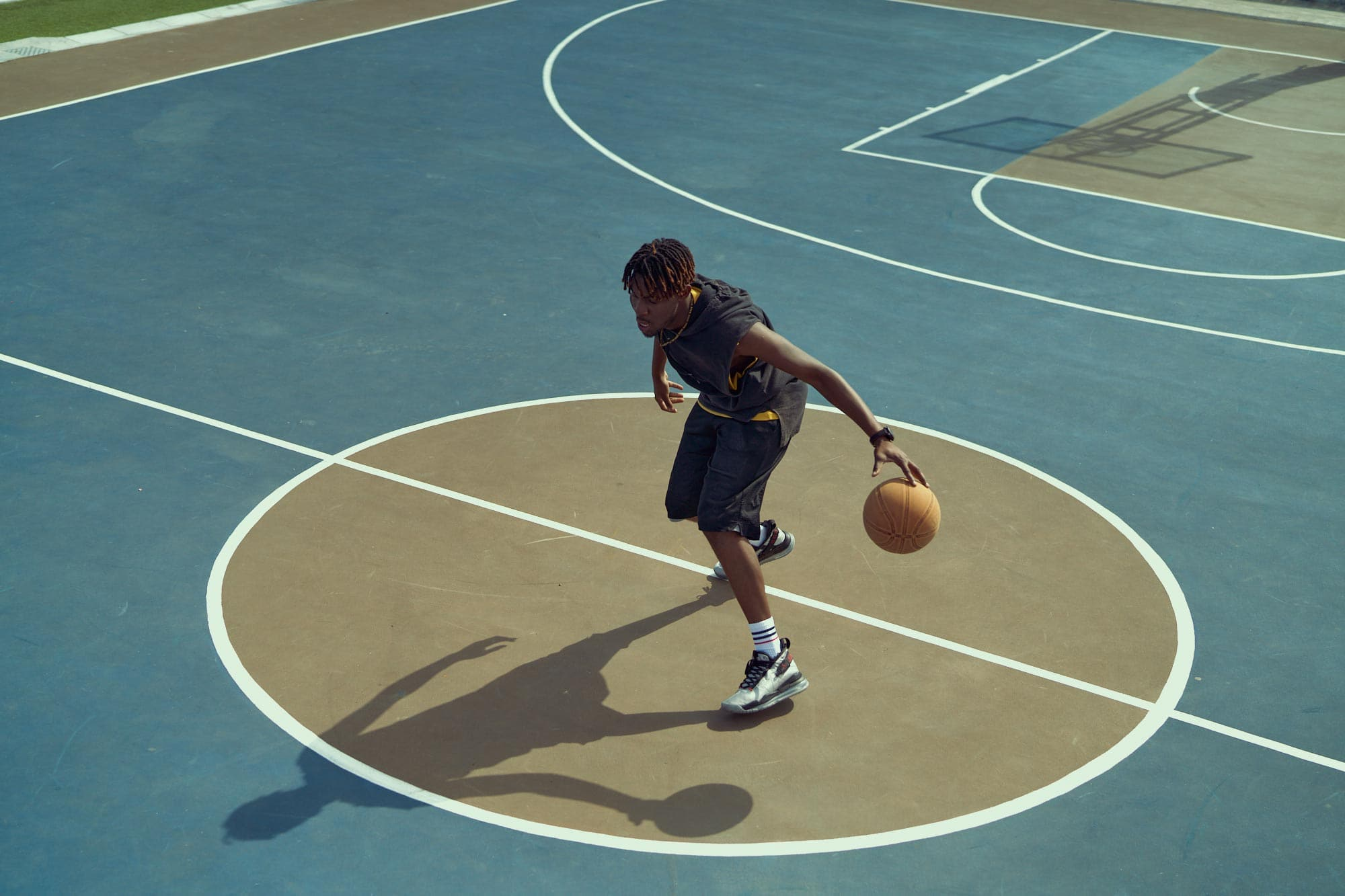 tissot t-touch swiss watch print campaign with basketball player on hard court using morning lighting